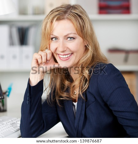 Happy mid adult businesswoman with hand on chin in office - stock photo