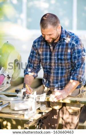 Happy mid adult carpenter marking on wood with pencil at table saw - stock photo