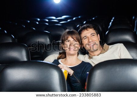 Happy mid adult couple watching film in cinema theater - stock photo