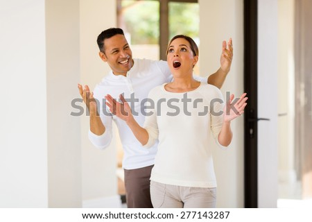 happy mid age man surprising his wife with a new house - stock photo