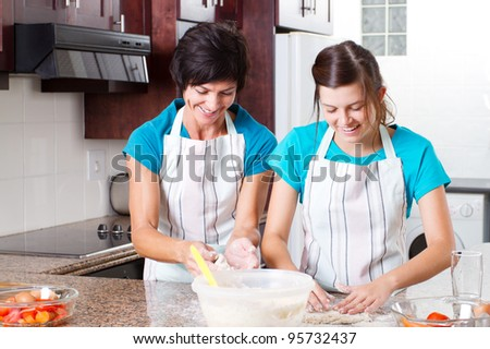 happy mid age mother and teen daughter baking in kitchen - stock photo