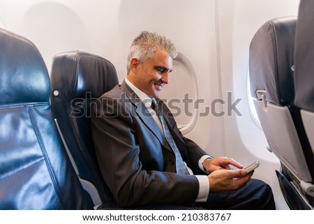 happy middle aged businessman using cell phone on airplane - stock photo