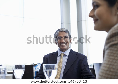Happy middle aged businessman with female colleague in restaurant - stock photo