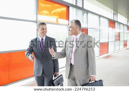 Happy middle aged businessmen talking while walking in railroad station - stock photo