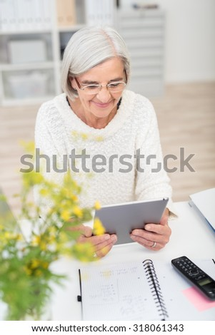 Happy Middle Aged Businesswoman Sitting at her Table and Using her Portable Tablet Computer. - stock photo