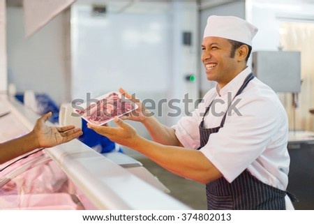 happy middle aged butcher serving customer in butchery - stock photo