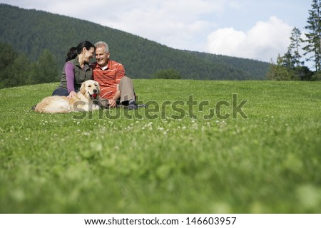 Happy middle aged couple and golden retriever relaxing on grass - stock photo
