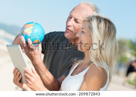 Happy middle-aged couple deciding on their next vacation standing on a beach consulting a globe and tablet computer as they check out global destinations - stock photo