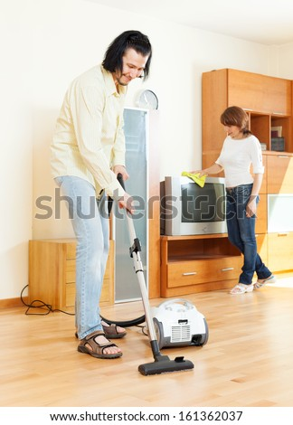 Happy middle-aged couple doing housework together  - stock photo