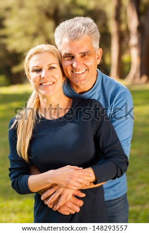 happy middle aged couple hugging outdoors - stock photo