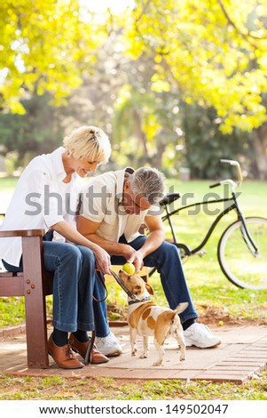 happy middle aged couple playing with their pet dog at the park - stock photo