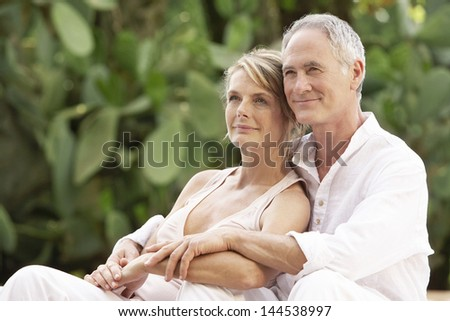 Happy middle aged couple with arms around relaxing in garden - stock photo