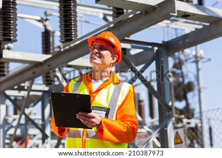 happy middle aged electrical engineer with clipboard in substation - stock photo
