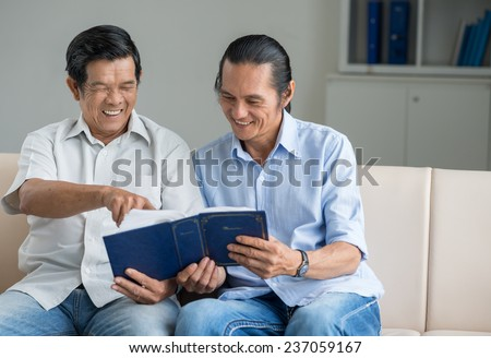 Happy middle-aged man and his father watching photo album - stock photo
