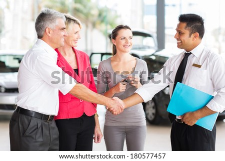 happy middle aged man handshake with car salesman after purchasing a car - stock photo