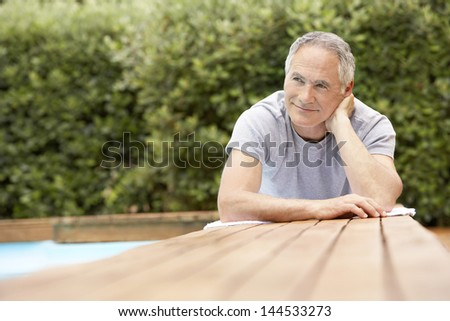Happy middle aged man reclining by poolside - stock photo