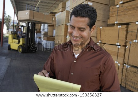 Happy middle aged man writing on notepad with worker working in forklift at warehouse - stock photo