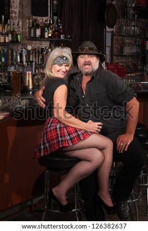 Happy middle aged motorcycle gang couple sitting at bar counter - stock photo