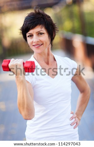 happy middle aged woman exercise with dumbbells - stock photo