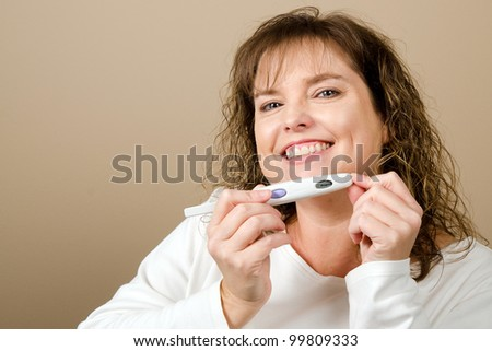 Happy middle-aged woman holding a positive pregnancy test with neutral copy space - stock photo