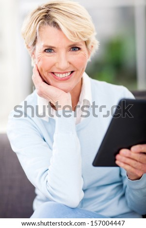 happy middle aged woman holding tablet pc at home - stock photo