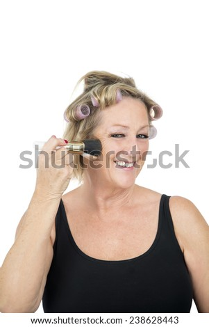 Happy middle aged woman using a makeup brush against a white background - stock photo
