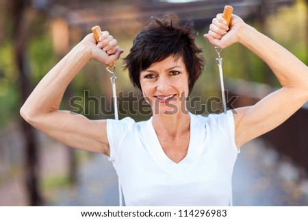 happy middle aged woman workout with jumping rope - stock photo