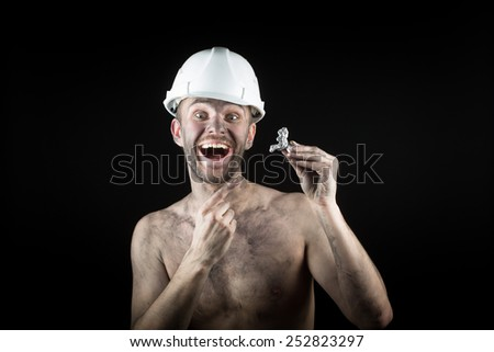 happy  miner shows a silver nugget  - stock photo