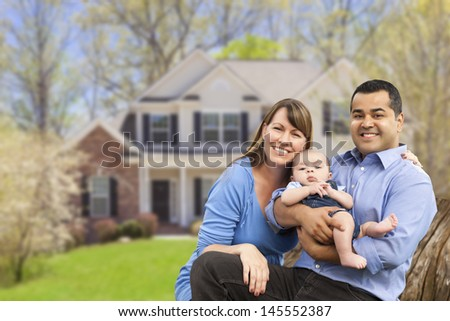 Happy Mixed Race Couple in Front of Beautiful House. - stock photo