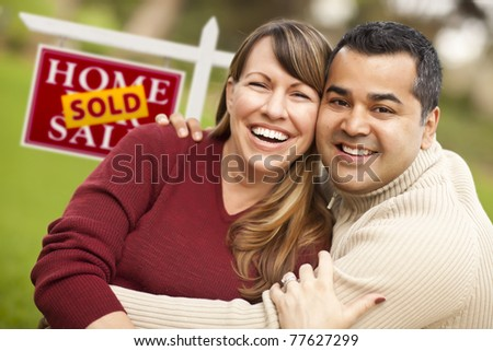 Happy Mixed Race Couple in Front of Sold Real Estate Sign. - stock photo
