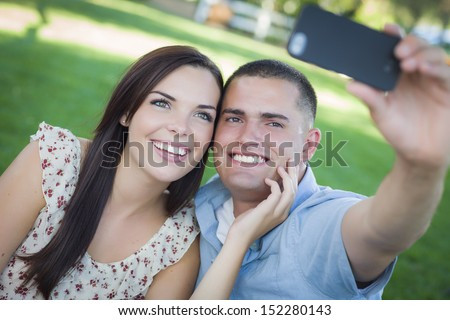 Happy Mixed Race Couple Taking Self Portrait with A Smart Phone in the Park. - stock photo