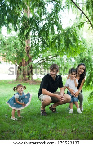 Happy, mixed race family hanging in the park. - stock photo