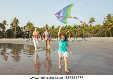 Happy mixed race family having fun on the beach at sunset. Parents playing with child. Child running on beach with kite in the hands - stock photo