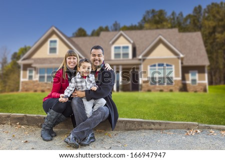 Happy Mixed Race Family in Front of Their Beautiful New Home. - stock photo