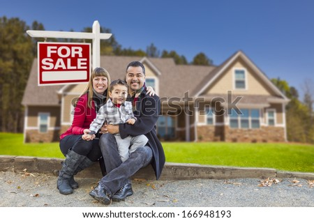 Happy Mixed Race Family in Front of Their New Home and a For Sale Real Estate Sign. - stock photo