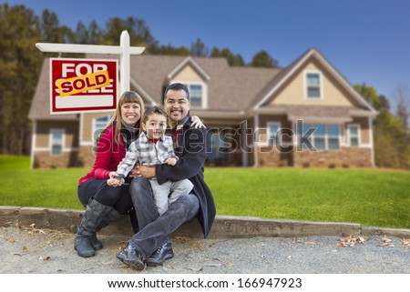 Happy Mixed Race Family in Front of Their New Home and a Sold For Sale Real Estate Sign. - stock photo