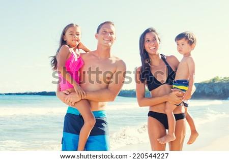 Happy Mixed Race Family of Four on Sunny Beach. Tropical Beach Family Vacation. - stock photo