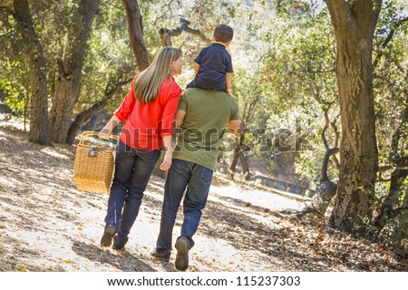 Happy Mixed Race Family with Picnic Basket Enjoy a Walk in the Park. - stock photo