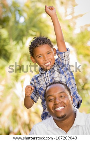 Happy Mixed Race Father and Son Cheering with Fist in the Air at the Park. - stock photo