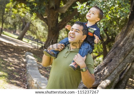 Happy Mixed Race Son Enjoys a Piggy Back Ride in the Park with Dad. - stock photo