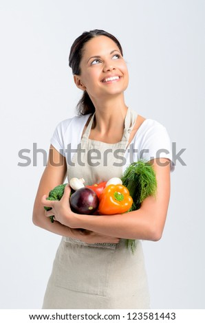 Happy mixed race woman in apron holding fresh organic vegetables in her hands and looking up on grey background, promoting healthy diet and lifestyle - stock photo