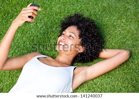 Happy mixed race woman on her cell phone in park - stock photo