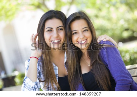 Happy Mixed Race Young Adult Female Friends Portrait Outside on Bench. - stock photo