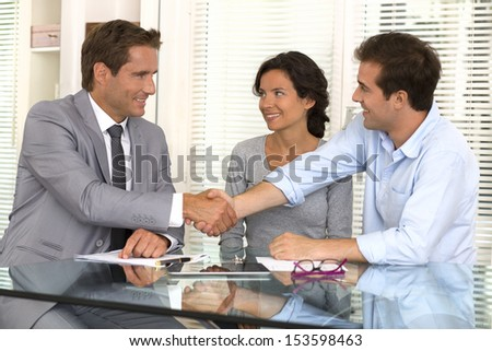 Happy modern couple seal a deal with their personal financial advisor , handshake , at home - stock photo