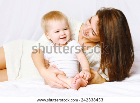 Happy mom and baby having fun in bed at home, life moment - stock photo