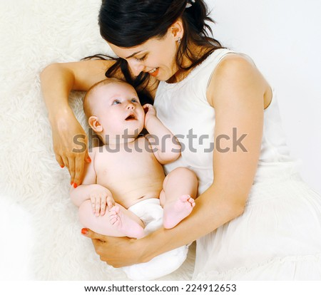 Happy mom and baby lying on the bed - stock photo