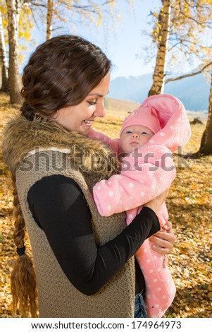 Happy mom and child girl hugging and laughing on nature fall. The concept of cheerful childhood and family. Beautiful Mother and her baby - stock photo
