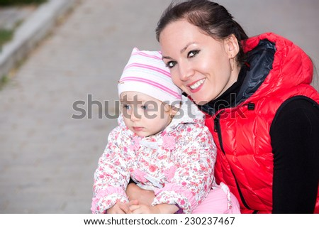 Happy mom and child girl hugging on nature The concept of childhood and family. Beautiful Mother and her baby outdoor - stock photo