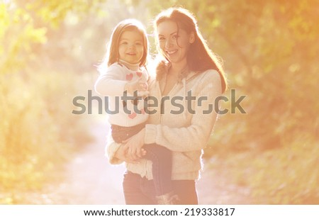 Happy mom and child outdoors in autumn park - stock photo