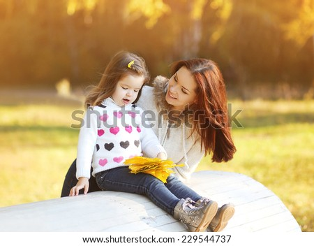Happy mom and daughter having fun outdoors in autumn park - stock photo